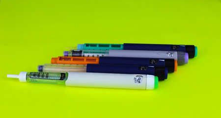 Different insulin syringe pens on a green background. Concept for diabetes compensation and insulin therapy.