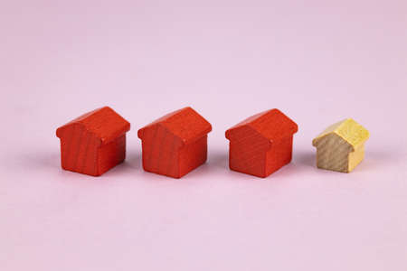 Three red toy houses and one wooden toy house on a pink background. Selective focus.