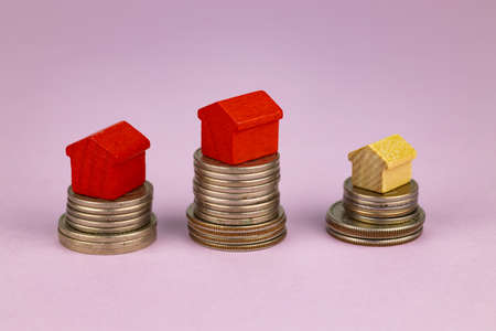 Stack of coins, toy houses on a pink background. Selective focus. Concept for sale, rent, house purchase, investment, mortgage, mortgage crisis. 免版税图像