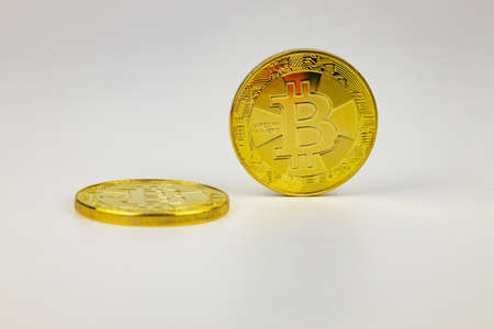 Two gold bitcoin coins on white background