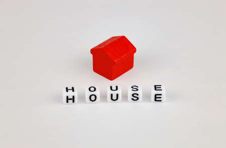 Toy red house and inscription from cubes - house, white background. Concept for buying, selling, renting, investing, home mortgages.