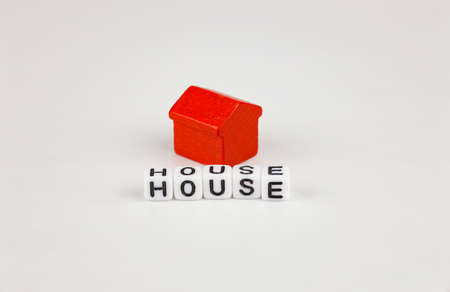 Toy red house, inscription with cubes - house, white background. 免版税图像
