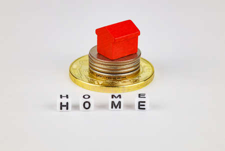 A toy red house stands on a stack of coins, a white background. Concept for buying, selling, renting, investing, home mortgages.