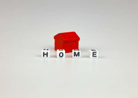 Toy red house, inscription with cubes - house, white background. Concept for sale, rent, investment, home mortgage. 免版税图像