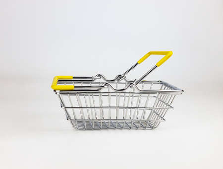 Shop basket with yellow handles on a white background