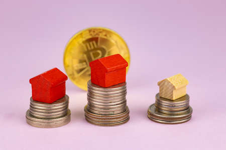 Stack of coins, bitcoin, toy houses on a pink background. Selective focus. Concept for sale, rent, house purchase, mortgage.