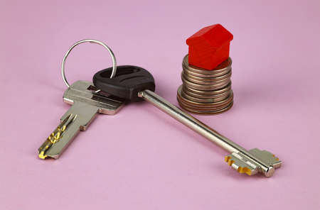 Stack of coins, toy house, house keys on a pink background. Selective focus. Concept for sale, rent, house purchase, mortgage.