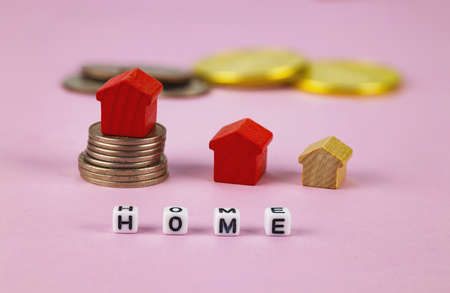Stacks of coins, toy houses on a pink background. Selective focus. Concept for selling, renting, buying a house, investment.