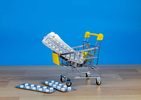 Medicine pills, tablets, blisters in a small supermarket shopping cart on blue background.