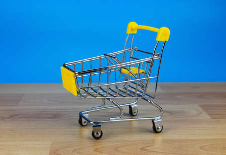 Small supermarket grocery push cart for shopping toy with wheels on blue background. Sale buy mall market shop consumer concept