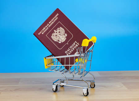 Russian passport in a shopping cart on a blue background