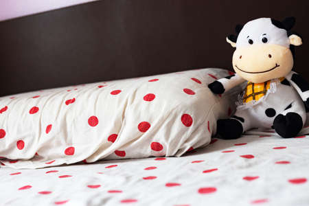 Close-up: a children's room, a bed with a pillow, next to a soft toy cow.
