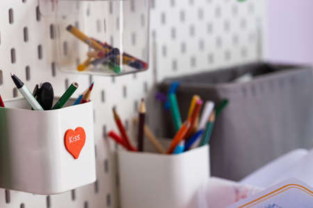 Pencil cup with pencils attached to the wall, design, school, close-up. 免版税图像