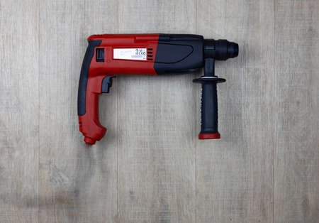 Red hammer drill on a wooden background