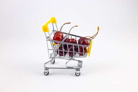 cherries in a shopping cart on a white background 免版税图像