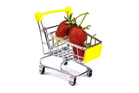 Small shopping cart full of fresh ripe strawberries isolated on white. Close-up, side view. 免版税图像