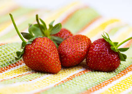 Fresh strawberries are lying on a towel. Close-up, selective focus.