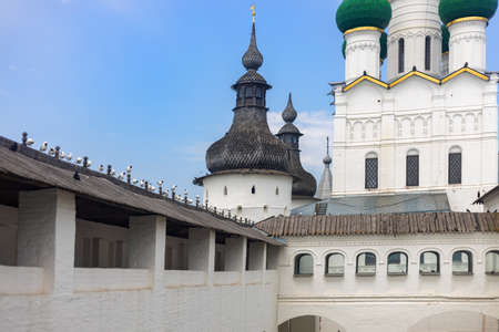 Orthodox church with a wooden dome. The protective wall of the Kremlin made of white stone in Rostov