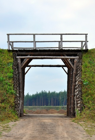 earthen wall: earthen wall with a wooden gate in it Stock Photo