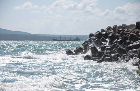 Sea breakawaters tetrapods. Sea landscape with mountains and ship