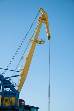 yellow port crane on blue sky background