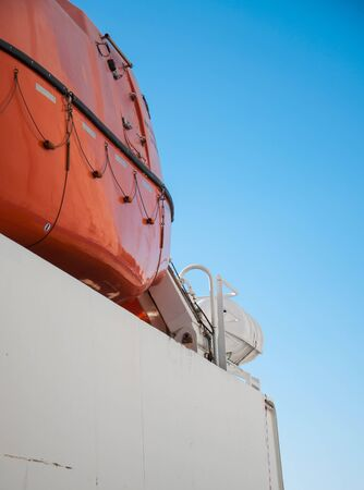 orange lifeboat anchored on board of a ship against blue sky