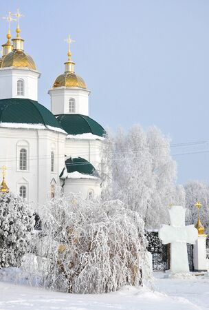 Orthodox church with ice cross in front of gate in winter park