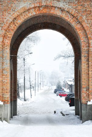 Brick arch in winter city with parking behind it