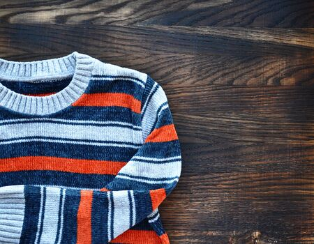 Striped sweater on wooden background. Top view.