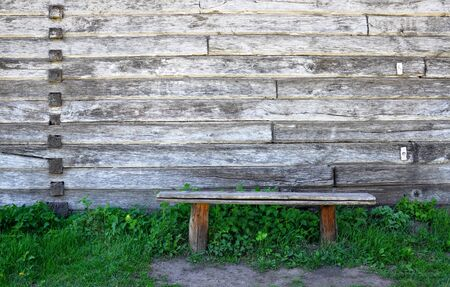 old wooden bench standing in the grass against the background of a wooden wall Banco de Imagens