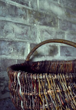 old wicker basket standing on the background of the brick wall