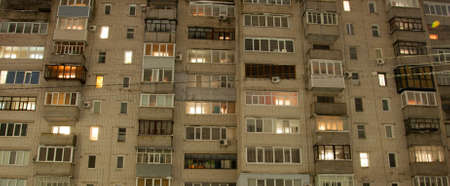Pryluky, Chernihiv, Ukraine - 02/15/2021: Multi-storey brick house in the evening with lights in the windows. Post-Soviet architecture of Eastern Europe
