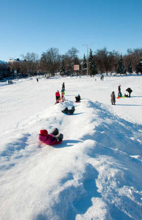 Pryluky, Chernihiv, Ukraine - 02/15/2021: Children ride with their parents on a snow slide in the city square. Sunny winter day
