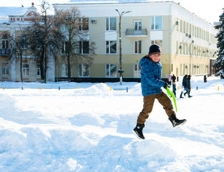 Pryluky, Chernihiv, Ukraine - 02/15/2021: Happy cheerful boy jumps on a snow slide. Winter fun in the city on a sunny winter day Editorial