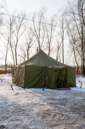 Pryluky, Chernihiv, Ukraine - 01/19/2021: Canvas tent on the bank of winter river. A place where you can warm up on a winter day Editorial