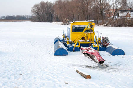 Pryluky, Chernihiv, Ukraine - 01/19/2021: Dredging machine on a frozen winter river. Cleaning the river bottom with a dredge