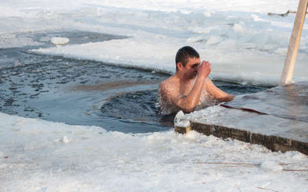 Pryluky, Chernihiv, Ukraine - 01 19 2021: Man dives in the  cross-shaped hole in a frozen river and crosses itself. Baptism of Jesus holiday Editorial