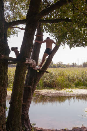 A young man stands on a tree above the river. Quality image for your project Stock Photo