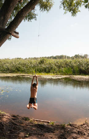 A young man jumping with bungee into the river. Quality image for your project