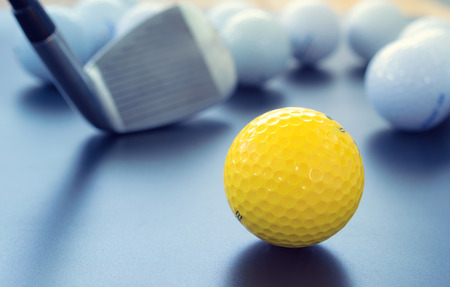 white and one yellow golf balls on black floor. individuality and difference concept. Stock Photo