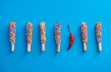 biscuit stick coated with rainbow and chilli on blue background Different or Unique business concepts.