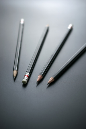 group of pencils on blackboard focus at pencil eraser, Concept sign for misconduct of management mistreating employees. Stock Photo