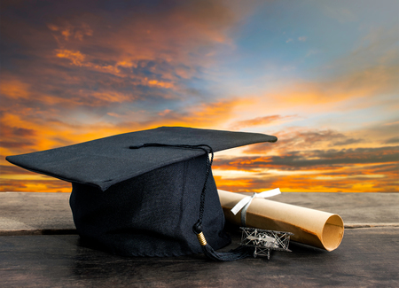 graduation cap, hat with degree paper on wood table, sunset sky background Empty ready for your product display or montage. Stock Photo