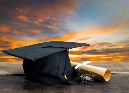 Graduation Cap, Hut mit Grad Papier auf Holztisch, Sonnenuntergang Himmel Hintergrund Leer bereit für Ihre Produktanzeige oder Montage.