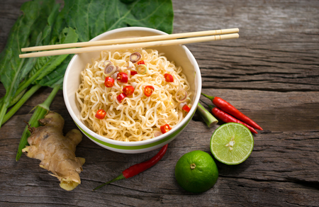 spicy Instant noodles with Vegetable in a bowl on wood board. Stock Photo