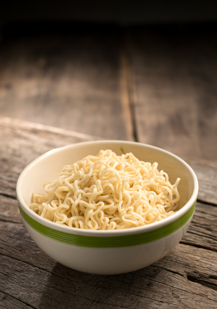Instant noodles in a bowl on wood board. Stock Photo