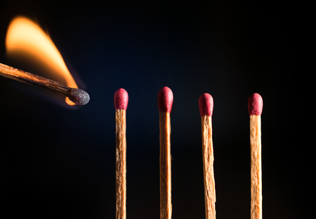 igniting: close-up of wooden match lighting up. Shot in studio Stock Photo