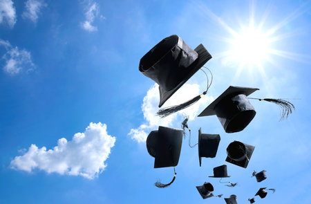 Graduation Ceremony, Graduation Caps, hat Thrown in the Air with bluesky abstract background. Stock Photo