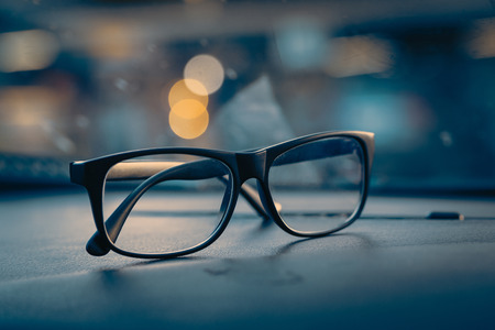 glasses on car console with city light Stock Photo