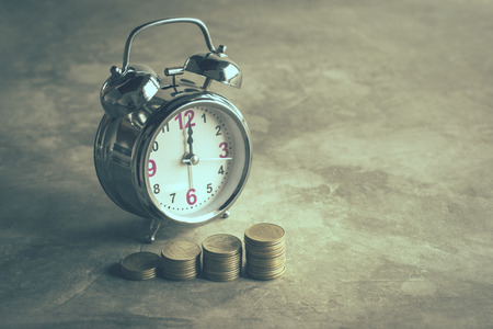 Stack of gold coins with alarm clock on cement floor in vintage tone.